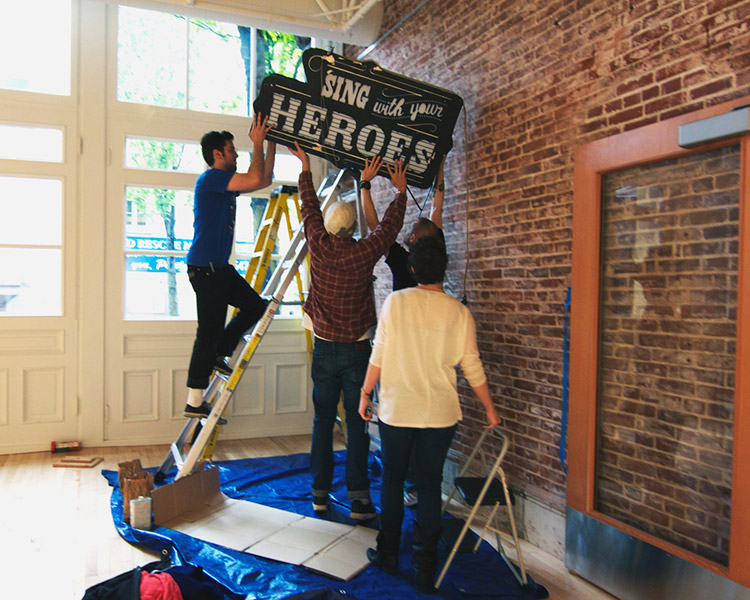 students hang Sing With Your Heroes sign