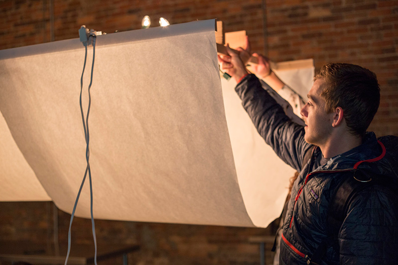 Zach Meyer holds up one end of a prototype lighting installation