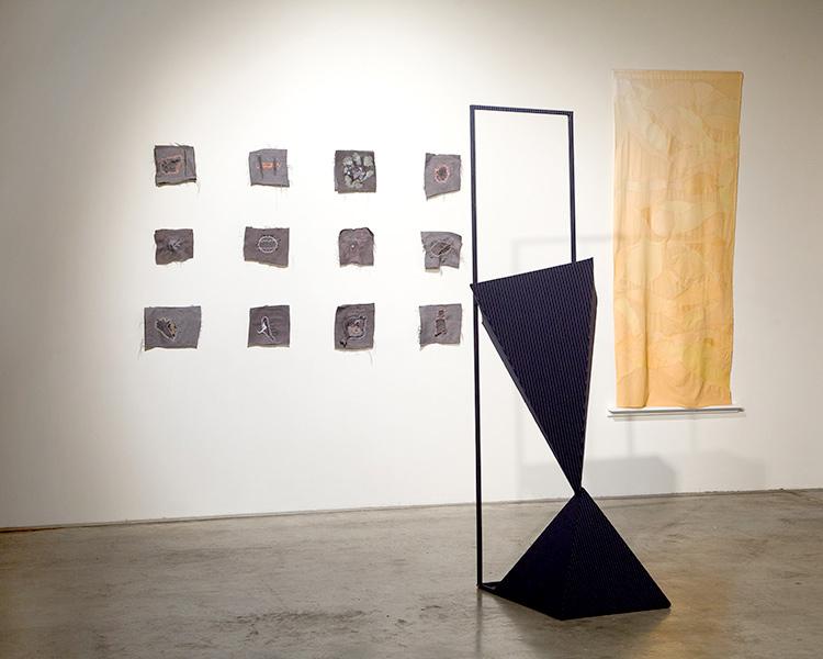 artwork: black scuplture and fabric wall art