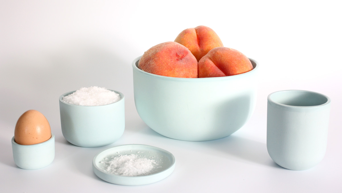 ceramic dishes by Julia Sherman and Thomas Sprott, containing peaches, salt, and an egg
