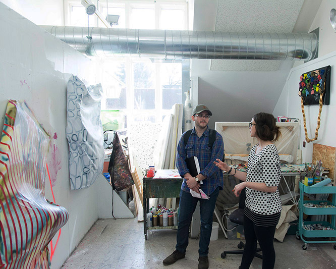 two people talk surrounded by art on walls