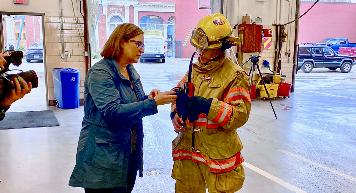 Susan Sokolowski inspects gloves with a firefighter