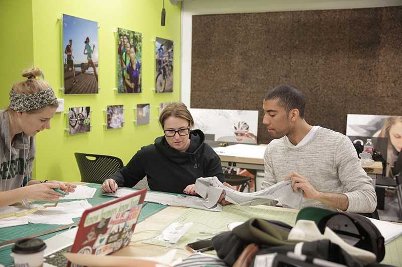 Brittany Lang (BS '16, product design), Associate Professor Susan Sokolowski, and product design student Austin Christianson discuss materials for a design.