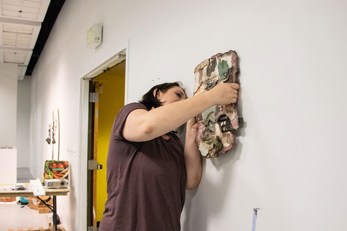 Lydia Mann hangs artwork