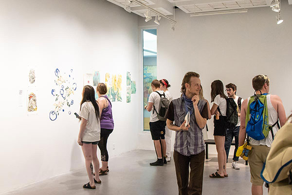 Families and friends gathere in the LaVerne Krause Gallery in Lawrence Hall to honor the work of Art + Design graduates.
