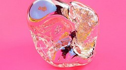 a mirror rock sculpture on pink background