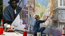 Artist working on a mural
