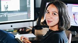 Portrait of alumna Mary Vertulfo at a desk