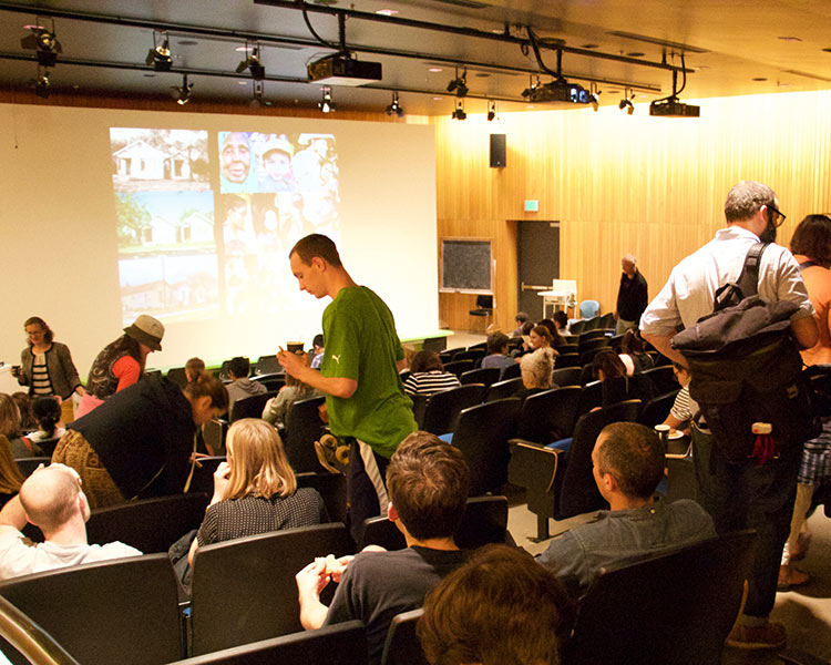 people gather in lecture hall for visiting artist lecture