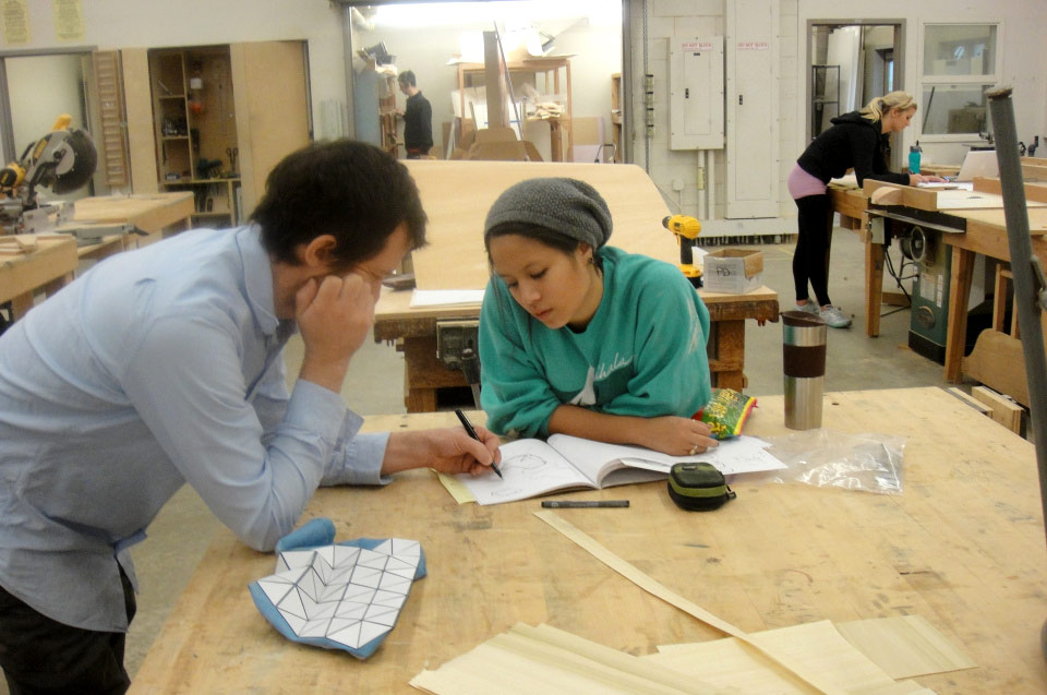 people discuss work in the woodshop