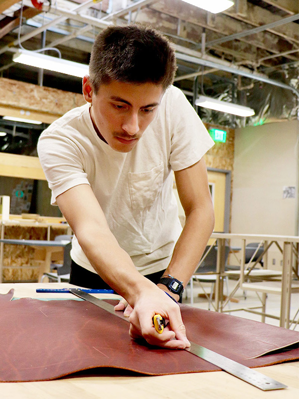 portrait of Xander Cuizon Tice cutting leather at a table